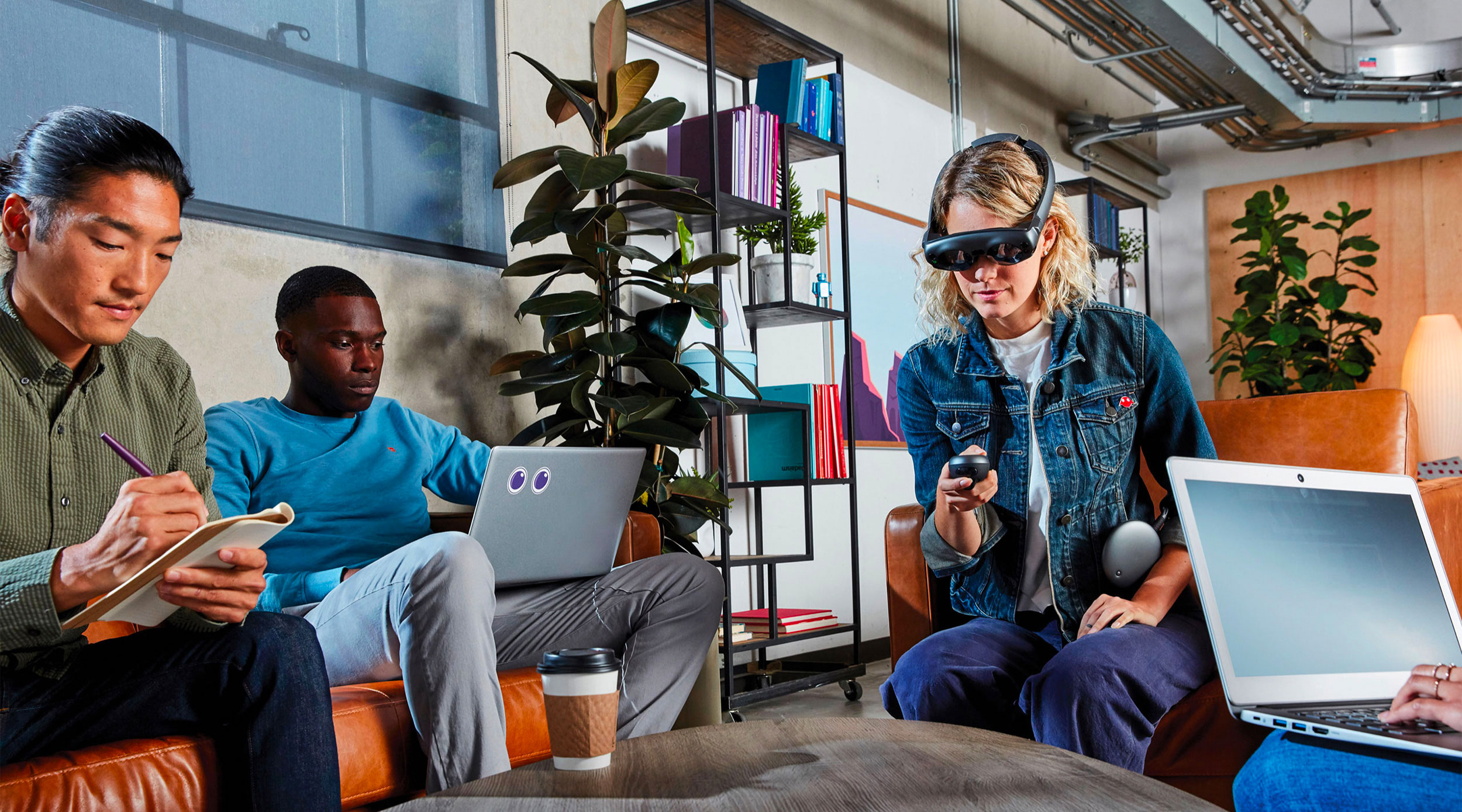 Blonde woman wearing the Magic Leap One headset sitting in an office with two male colleagues at work.