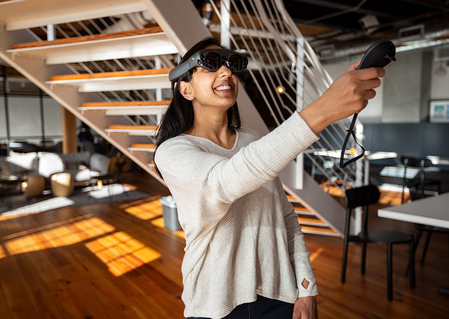 Smiling woman wearing Magic Leap headset in office and holding controller up in front of her.