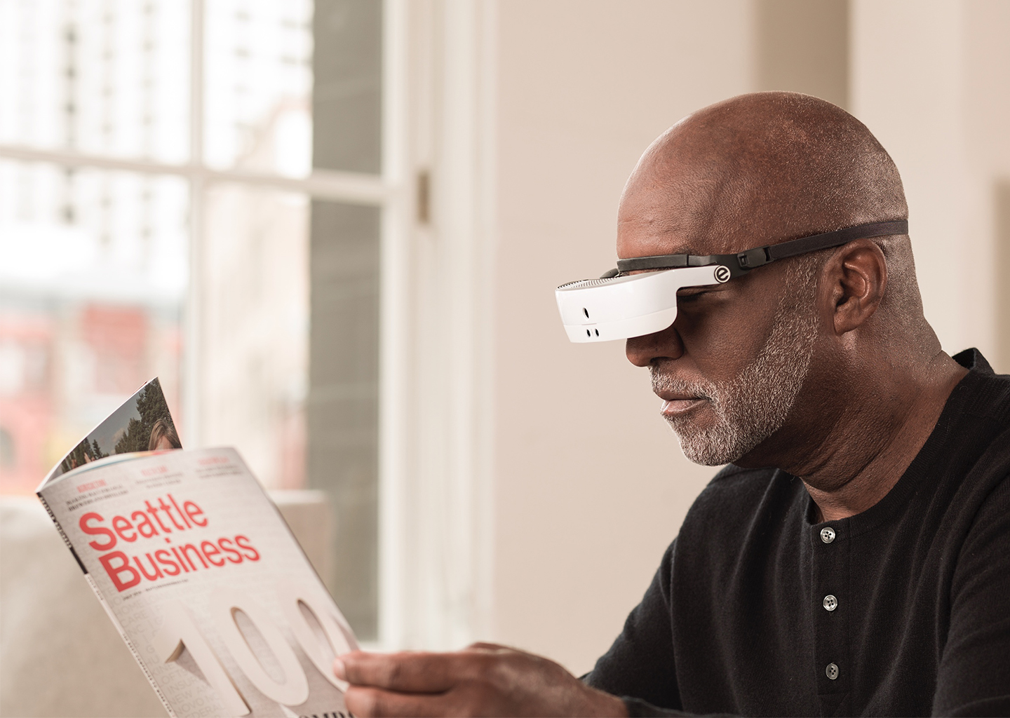 Senior black man wearing eSight headset reading a magazine.
