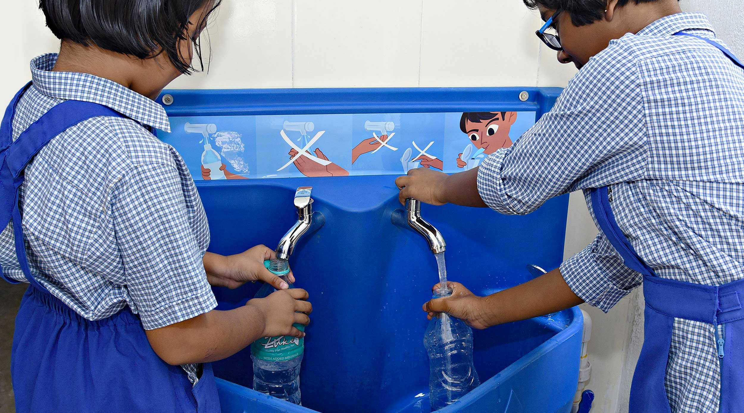 Two young girls in India wearing school uniforms and filling plastic water bottles from a blue Splash drinking water station.