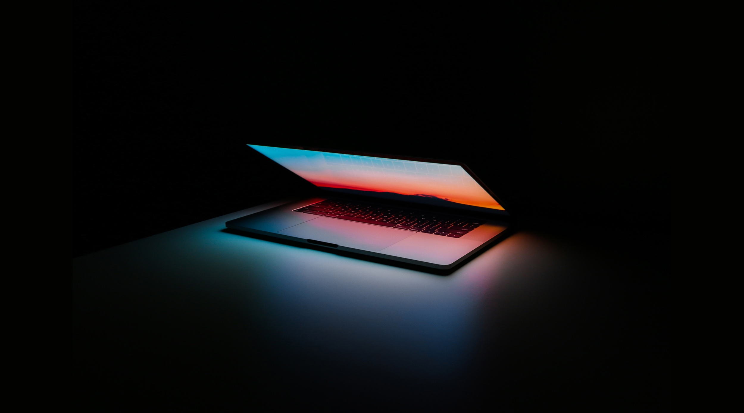 Laptop open and ominously glowing against a dark background.
